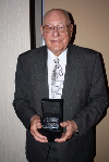 Elderly man with glasses wearing a gray suit with white dress shirt holding his Legacy of Community Banking award
