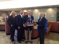 Star Bank Board of Directors being presented a folded American flag at a 110 years in banking ceremony