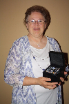 A middle aged woman with glasses holding her Legacy of Community Banking award