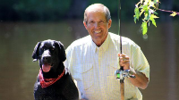 Ron Schara fishing with his black labrador, Raven